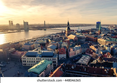 Riga, Latvia: aerial panoramic top view of Old Town and Daugava River at sunset. The tower of Dome Cathedral, a symbol of the Latvian capital city.