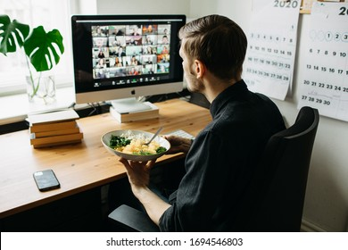 Riga, Latvia - April 04 2020: Man having lunch at the table in home office while having Zoom video conference call via computer. Stay at home and work from home concept during Coronavirus pandemic
