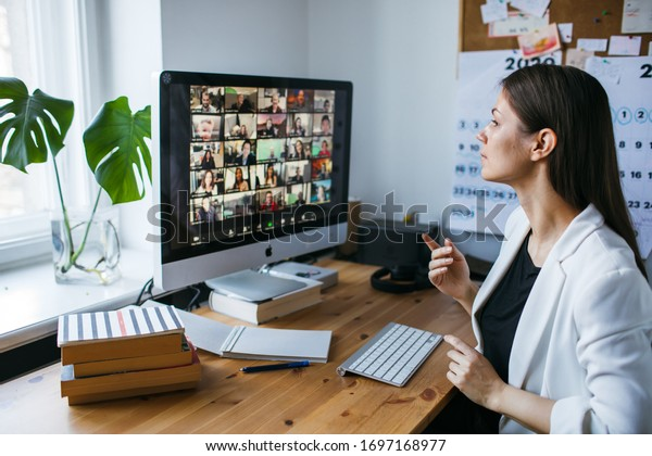 Riga, Latvia - April 04 2020: Beautiful young woman having Zoom video conference call via computer. Zoom Call Meeting. Home office. Stay at home and work from home concept during Coronavirus pandemic