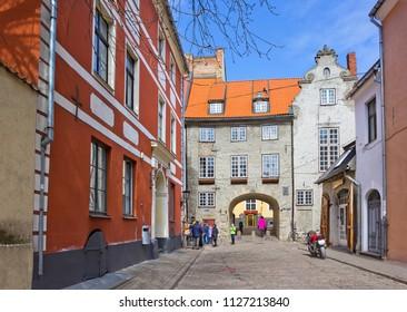 Riga, Latvia - April 19, 2018: Small street leading to medieval gate