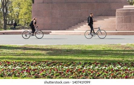 Riga, Latvia, April 2019 - Person showing his skills using handphone without holding bicycle handle bar whilst cycling.
