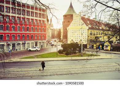 RIGA, LATVIA - APRIL 25, 2017: A woman with a dog crossing the Zigfrida Annas Meierovica bulvaris street on April 25, 2017 in Riga, Latvia. Top aerial view. Old town in Riga. Retro vintage style.