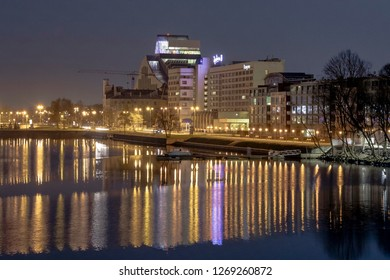 Riga, Latvia - april 29, 2018: Evening Cityscape At Bank Of Daugava River. Urban View Of National Library Building and Radisson Blue Daugava. Night photo.