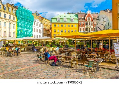 RIGA, LATVIA, AUGUST 15, 2016: People are strolling through Doma Laukums square full of restaurants in the Latvian capital Riga.
