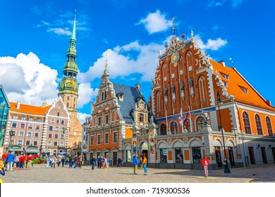 RIGA, LATVIA, AUGUST 15, 2016: Ratslaukums square with St Peters church and House of Blackheads in old town of Riga in Latvia.