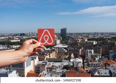 Riga, Latvia. August, 2019.  Travel around the world with Airbnb. Logo Airbnb and the city on the background. Home concept. Man holds the logo of a popular company.