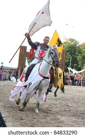 RIGA, LATVIA - AUGUST 21: Member of The Devils Horsemen stunt team riding horse and holding flag during Riga Festival on August 21, 2011 in Riga, Latvia