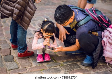 RIGA, LATVIA - AUGUST 27, 2017: Chinese father and daughter look at the phone. Riga, Latvia - August 27.