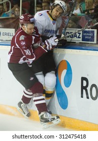 RIGA, LATVIA - AUGUST 27: Miks Indrasis (70) and Nikolai Stasenko (5) crash in to boards in KHL game between Dinamo Riga and Severstal Cherepovets played on AUGUST 27, 2015 in Arena Riga