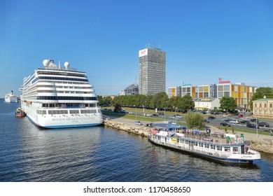 """RIGA, LATVIA, August 30, 2018: The cruise ship """"Seven Seas Explorer"""" in Riga Passenger Port and touristic river boat """"Rigas Perle"""" (Pearl of Riga)."""