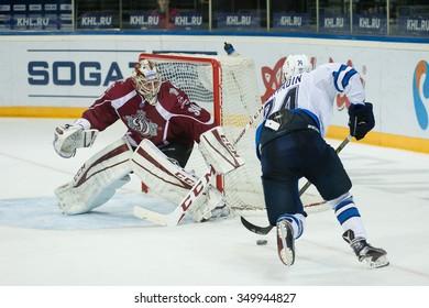 RIGA, LATVIA - DECEMBER 10: Goalie of Joacim Eriksson (30) saves the goal of Pavel Poryadin (24) in KHL game between Dinamo Riga and Neftekhimik Nizhnekamsk played on DECEMBER 10, 2015 in Arena Riga