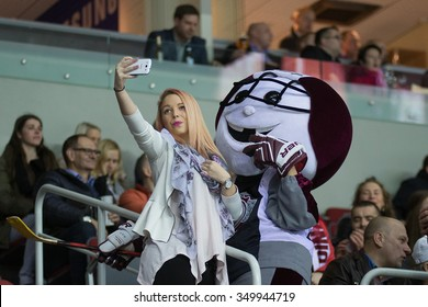 RIGA, LATVIA - DECEMBER 10: Supporter of Dinamo Riga takes selfie with a mascot of the team in KHL game between Dinamo Riga and Neftekhimik Nizhnekamsk played on DECEMBER 10, 2015 in Arena Riga
