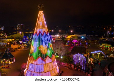 """Riga, Latvia. December 24, 2019. Beautiful Christmas mood at the """"Lido"""" restaurant with a huge Christmas tree decorated with led lamps and ice skating park at dusk.Christmas tree view."""