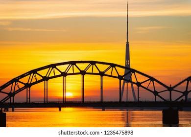 Riga, Latvia - December 27, 2017: Romantic sunrise at Vansu Bridge over Daugava River in Riga in Latvia.