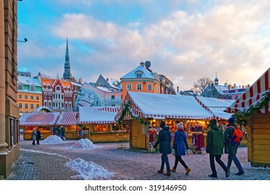 RIGA, LATVIA - DECEMBER 28, 2014: People stroll down an aisle at the Christmas Market held at Riga's Old Town (Dome square) on December 28, 2014. Latvia