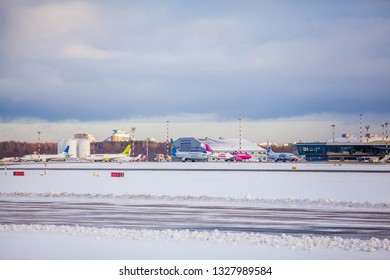 Riga, Latvia - January 16, 2019:  RIX Airport. Aircrafts are parked next to a hangar for the next flight. airBaltic, Ukraine International Boeing, Hungarian Wizzair, Russian Utair, ASL Airline.