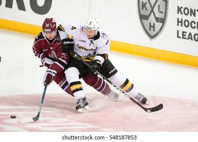 RIGA, LATVIA - JANUARY 3: Clay Wilson (4) tries to stop Edgars Kulda (32) in the KHL regular championship game between Dinamo Riga and Severstal Cherepovets, played on January 3, 2017 in Arena Riga