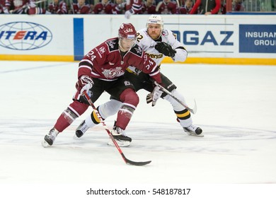 RIGA, LATVIA - JANUARY 3: Pyotr Schastlivy (24) tries to protect the puck from Denis Yezhov (82) in the KHL game between Dinamo Riga and Severstal Cherepovets, played on January 3, 2017 in Arena Riga