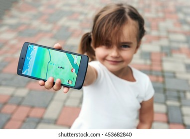 Riga, Latvia- July 17, 2016: Little girl playing a Pokemon Go game outdoors. Pokemon Go is a popular virtual reality game for mobile devices