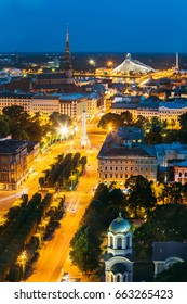 Riga, Latvia - July 2, 2016: Aerial View Of Cityscape In Evening Night Lights Illumination. Summer Top View Of St. Peter's Church, Boulevard Of Freedom, Freedom Monument And Latvian National Library