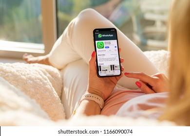 Riga, Latvia - July 21, 2018: Woman looking at WhatsApp on mobile phone.