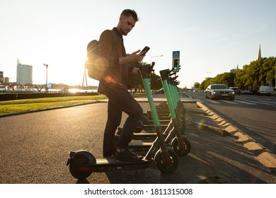 Riga, Latvia - July 26 2020: Young man unlocks an e-scooter with his mobile phone. Electric scooter new way of city mobility. Green transportation. Sustainable climate neutral cities goals