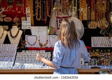 RIGA, LATVIA - JULY 31, 2018:  A woman in the souvenir kiosk choose amber jewelry.
