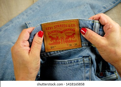 RIGA, LATVIA - june 01, 2019: Woman's hand with red nails taking out label logo from pocket of Levi's Jeans. Levi Strauss &Co. is a American clothing company was founded in 1853.