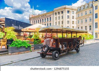 RIGA, LATVIA JUNE 16, 2017: Mobile Beer Pub on the street of the old Riga. Original transport - a car with a bicycle drive.