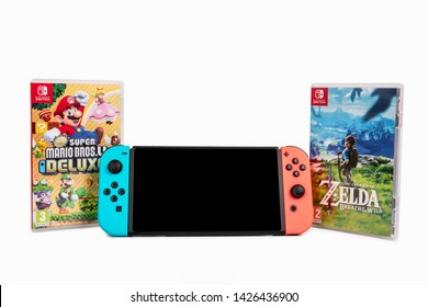 Riga, Latvia -  June 17, 2019: Nintendo Switch, the video game console for home or portable gaming. Game The Legend of Zelda and Super Mario Bros.U. White background
