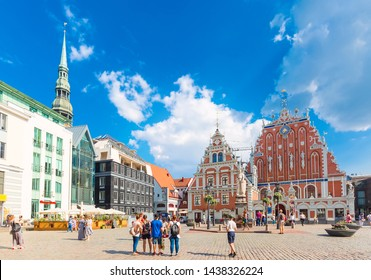 Riga, Latvia - June, 2018: View of the Old Town Ratslaukums square, Roland Statue, The Blackheads House near St Peters Cathedral against blue sky in Riga, Latvia. Summer sunny day