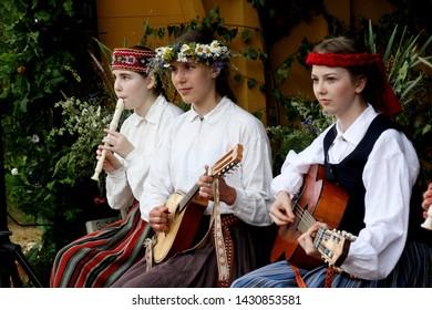 Riga, Latvia - june 21, 2019: LIGO celebration of the midsummer in Latvia. Midsummer night magic in Rubeni hill meadow with folklor group Skandinieki and Kokle