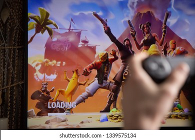 Riga, Latvia - March 14, 2019: Fortnite loading screen seen on the TV and hands holding video game controller in the foreground. Fortnite is an online video game developed by Epic Games.