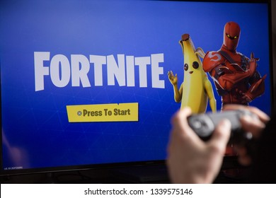 Riga, Latvia - March 14, 2019: Hands holding joystick controller and Fortnite main loading screen seen in the background on the TV. Fortnite is a multiplayer video game developed by Epic Games.