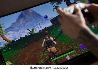 Riga, Latvia - March 14, 2019: Tattooed hands holding joystick controller playing Fortnite. Fortnite is an online video game developed by Epic Games.