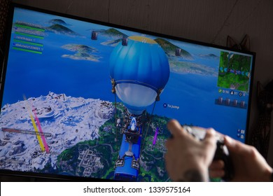 Riga, Latvia - March 14, 2019: A person with tattooed hand playing Fortnite video game on big TV screen. Fortnite is an online video game created by Epic Games.
