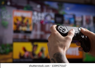 Riga, Latvia - March 14, 2019: Tattooed hands holding playstation console controller with Fortnite game logo seen on the TV in the background. Fortnite is an online video game developed by Epic Games.