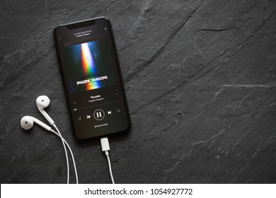 Riga, Latvia - March 25, 2018: iPhone X playing song Thunder by Imagine Dragons on Spotify app.
