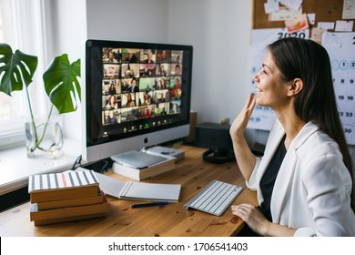 Riga, Latvia - March 28 2020: Young woman having video Zoom call via computer in the home office. Remote teem meeting Stay at home and work from home concept. Manage Online office