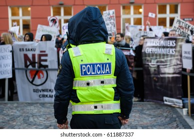 RIGA, LATVIA - March 30, 2017. Policeman standing before crowd, who are protesting against wildlife animal using at Circus, near Parliament of Latvia, in Riga , Latvia.