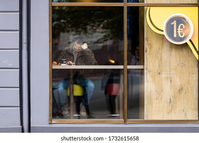 Riga, Latvia - May 14, 2020: view through the window of a man in a cafe writing a message on a smartphone and drinking coffee