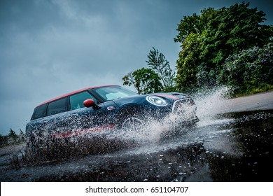 RIGA, LATVIA - MAY 31st, 2017: 2017 MINI CLUBMAN JOHN COOPER WORKS tests in rainy day. Car passing big puddle on high speed.