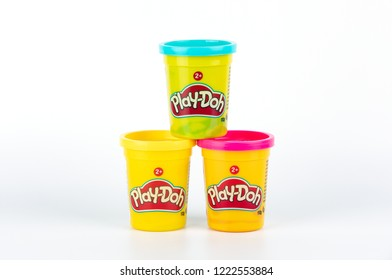 Riga, Latvia - November 05, 2018: Play-Doh clay in a yellow small container with Red, Yellow and Blue cover on white background