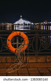 RIGA, LATVIA - NOVEMBER 17, 2017: Orange lifebuoy attached to railings of river Daugava promenade with illuminated Latvian National Library building on background.