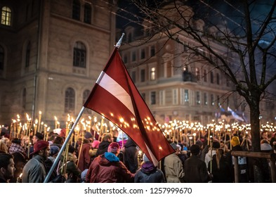 Riga, Latvia - November 18, 2018: Raising the flag of Latvia during annual torchlight procession to commemorate Latvian independence Day.