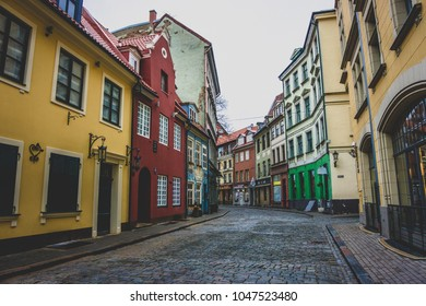 RIGA, LATVIA - NOVEMBER 23, 2017: Colorful buildings on a winding cobblestone street in Old Town, Riga