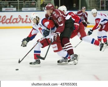 RIGA, LATVIA - NOVEMBER 26: Mikhail Grigoryev (4) of Lokomotiv Yaroslavl stops Gints Meija (87) in KHL game between Dinamo Riga and Lokomotiv Yaroslavl played on NOVEMBER 26, 2015 in Arena Riga
