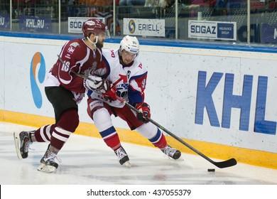 RIGA, LATVIA - NOVEMBER 26: Steven Seigo (16) of Dinamo Riga tries to stop Andrei Loktionov (95) in KHL game between Dinamo Riga and Lokomotiv Yaroslavl played on NOVEMBER 26, 2015 in Arena Riga