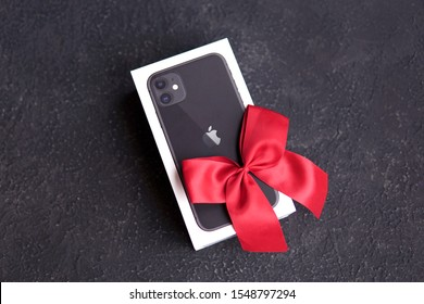 Riga, Latvia - November 3 2019: a box of new black Apple iPhone 11 with red bow like a gift on black background. The latest model of Apple mobile phones. Copy space.