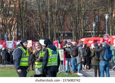 Riga, Latvia - November 30, 2019 : Police man speaking to man during Animal Advocacy event with NO FUR signs and banners in hands protest against fur farming, ask to ban animal fur industry